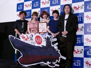 プレゼントの夫婦の似顔絵を手にする神田沙也加(中央)と登壇者たち